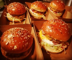 Cinq hamburgers présentés dans leurs boites